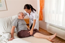 caregiver helping her patient in bed